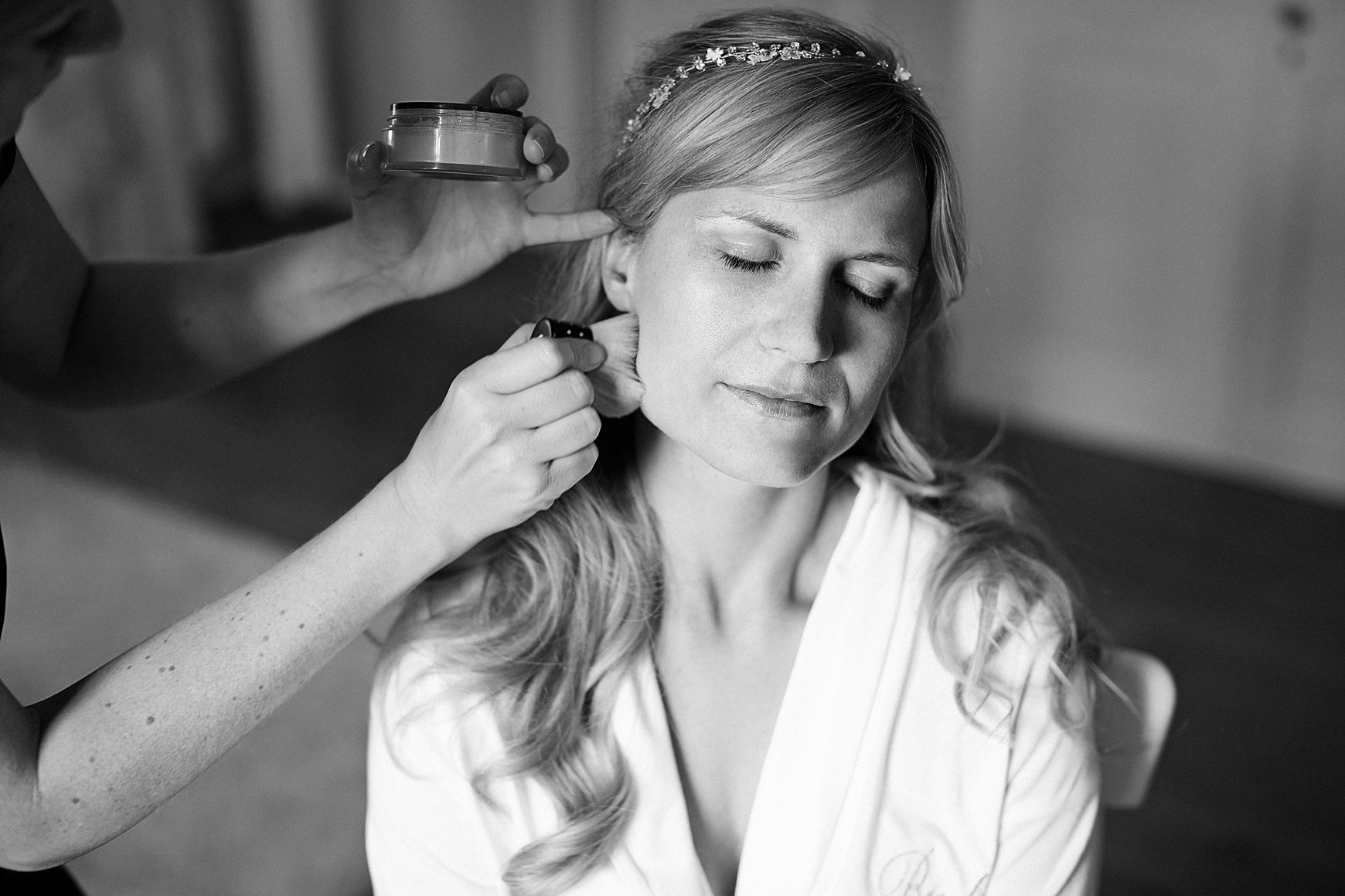 Eine Frau mit langen blonden Haaren wird geschminkt