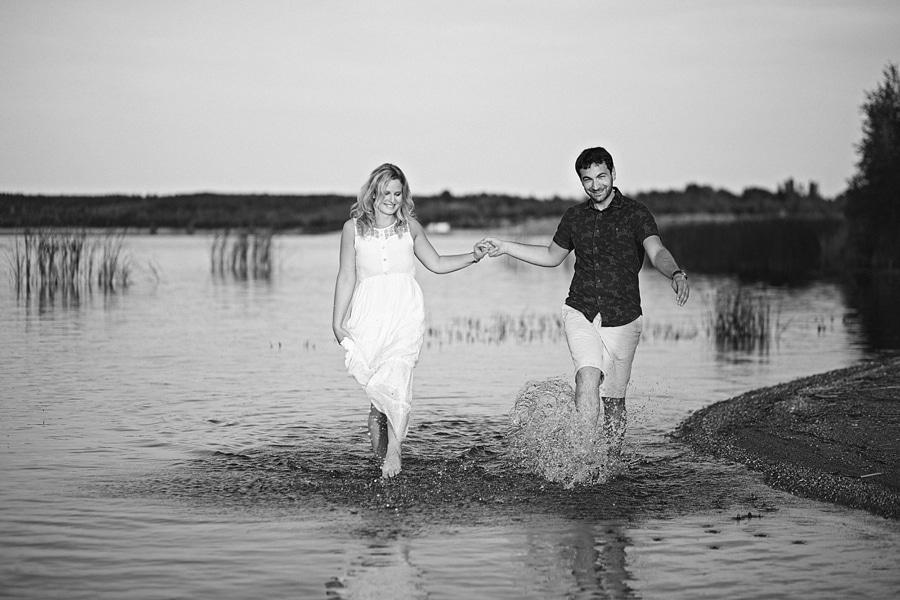 Eine junges Paar geht händchenhaltend durchs Wasser