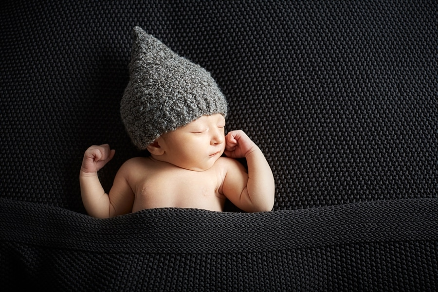 Ein Neugeborenes mit einer Mütze schläft auf einer dunklen Decke
