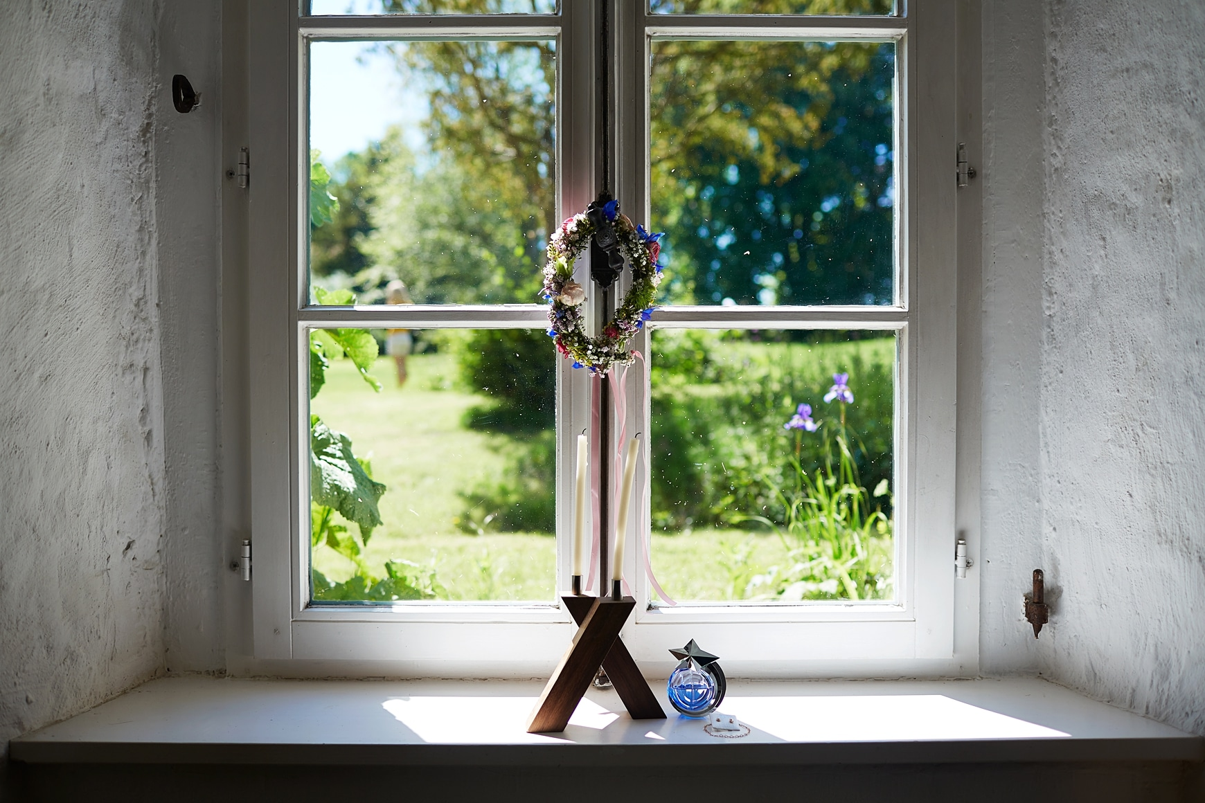 Ein Blumenkranz der an einem Fenster hängt