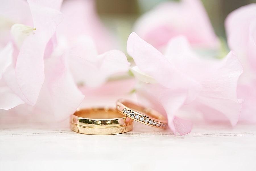 Goldene Eheringe unter Blüten vom Hochzeitsfotograf fotografiert