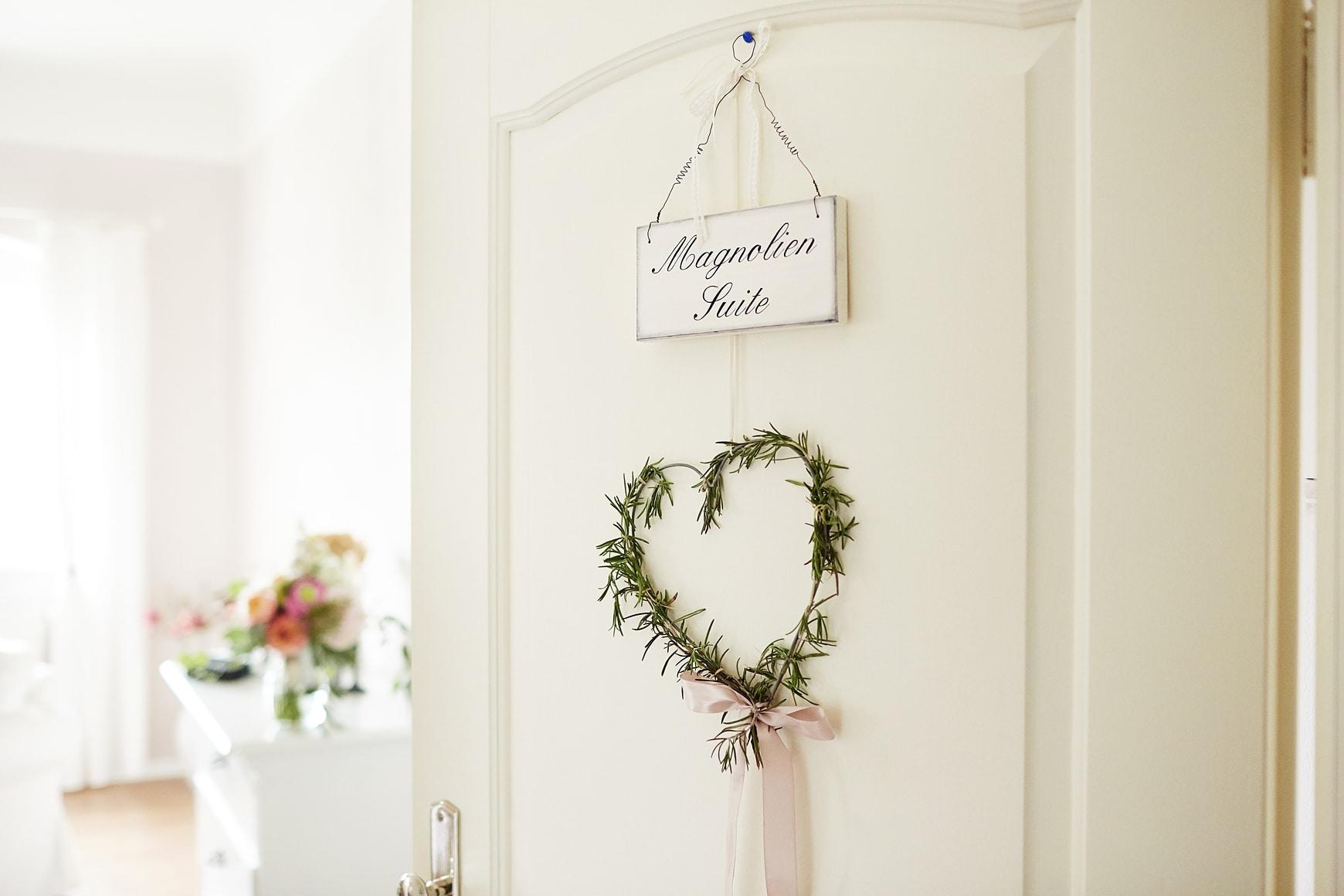 Der Eingang einer Suite mit Blumenkranz