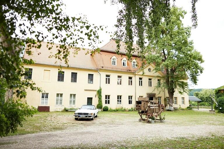 Ein altes Hofgebäude vor dem ein alter Mercedes steht