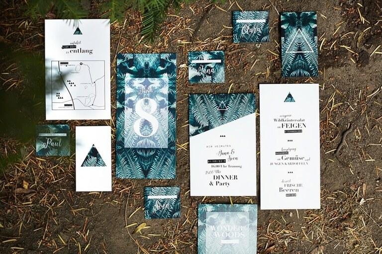 Moderne Hochzeitspapeterie in grün auf einem Waldboden liegend von Karina Gold
