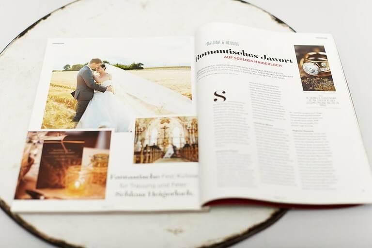 Ein aufgeschlagenes Hochzeitsmagazin mit einem Bild von einem Brautpaar im Kornfeld