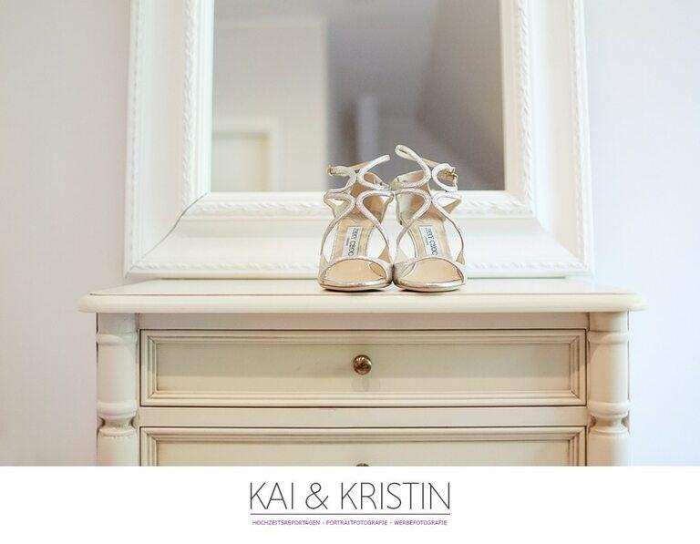 Brautschuhe auf einem Schrank vor einem Spiegel