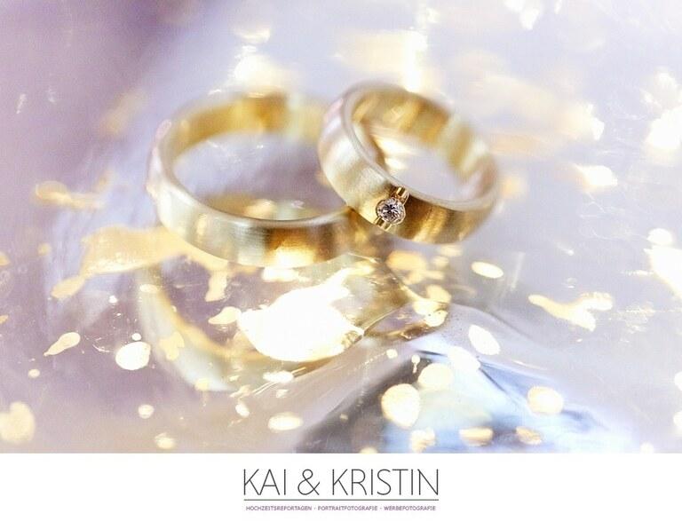 Goldene Eheringe auf einer Spiegelnden und reflektierenden Oberfläche