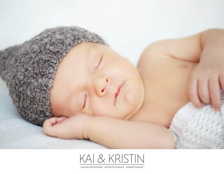 Ein Neugeborenes mit einer Mütze liegt auf der Seite und schläft