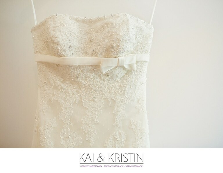 Ein Brautkleid hängt vor einer weißen Wand