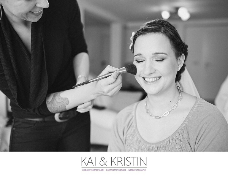 Eine Braut lächelt mit geschlossenen Augen während Sie geschminkt wird