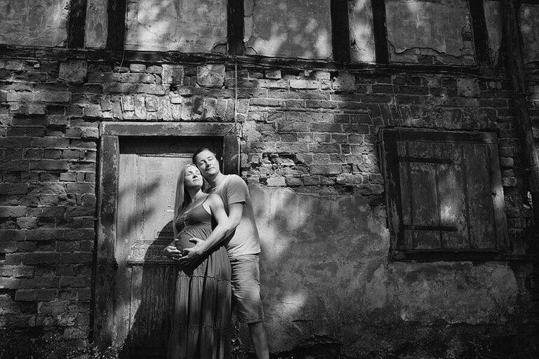 Eine Schwangere posiert mit ihrem Partner  vor einer Mauer für tolle Babybauchfotos