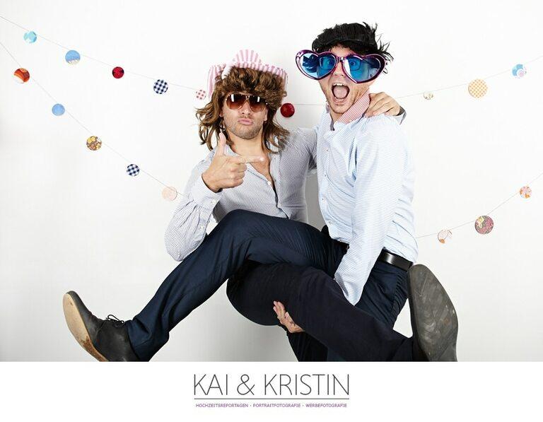 Zwei Männer in lustigen Outfits vor einer weißen Wand als Photo Booth