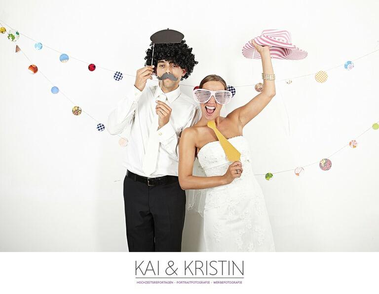 Ein Brautpaar steht verkleidet vor einem Photobooth