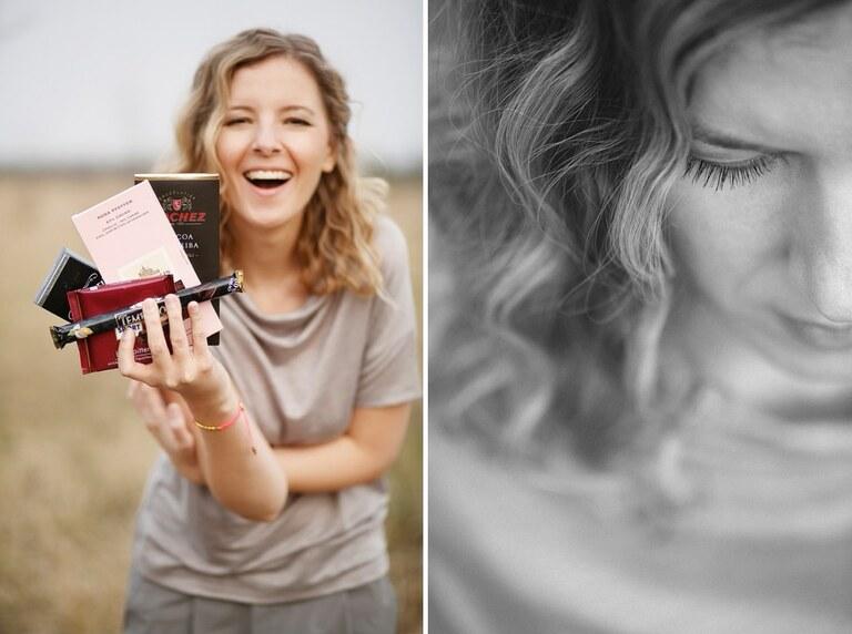 Eine Frau hält verschiedenen Tafeln Schokolade lachend in die Kamera
