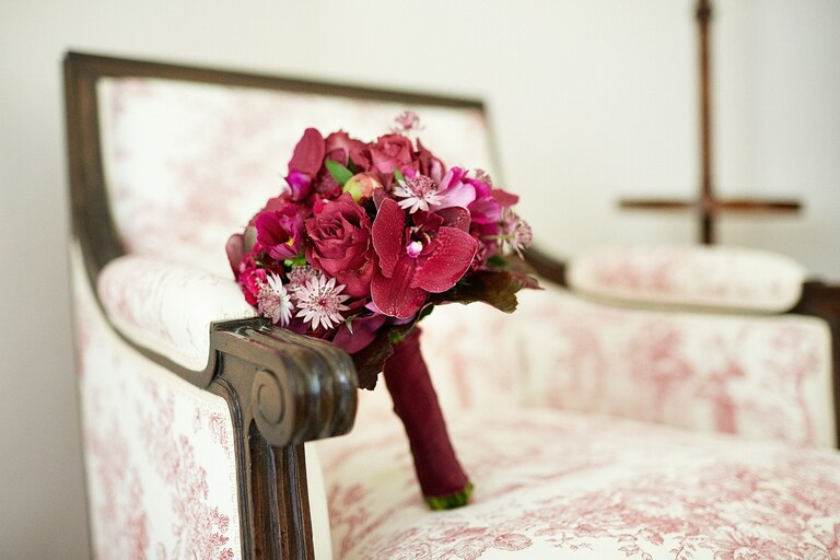 Ein Brautstrauß in Rot auf einem Sessel auf einer Hochzeit im Schlosshotel Münchhausen
