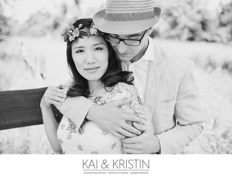 Ein Mann mit Hut umarmt seine Frau von hinten und diese schaut entspannt in die Kamera