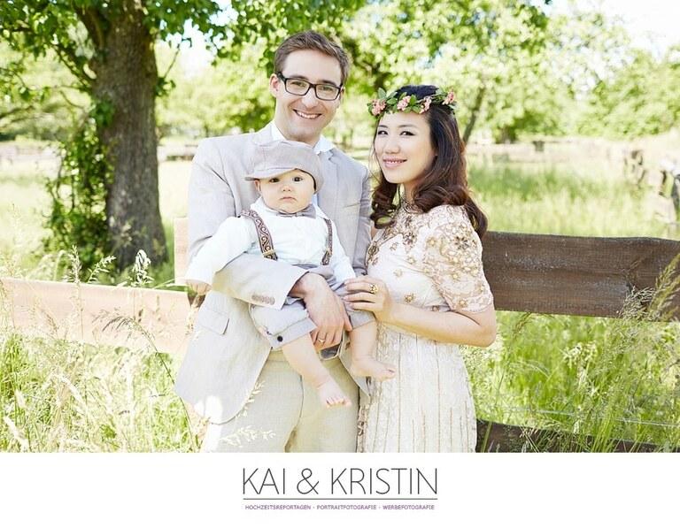 Ein Ehepaar posiert mit ihrem Sohn auf dem Arm für ihre After Wedding Fotos während des After Wedding Shooting