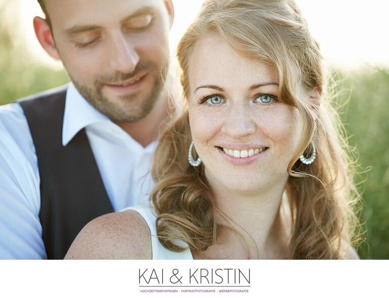 Eine Frau mit blauen Augen steht vor ihrem Mann im Gegenlicht und lächelt in die Kamera