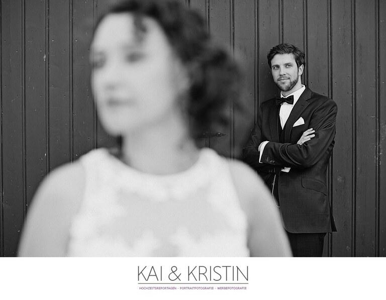 Ein Bräutigam steht mit verschränkten Armen hinter seiner Braut