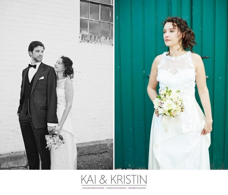 Eine Braut hält ihren Brautstrauß in der rechten Hand während sie vor einem grünen Holztor steht