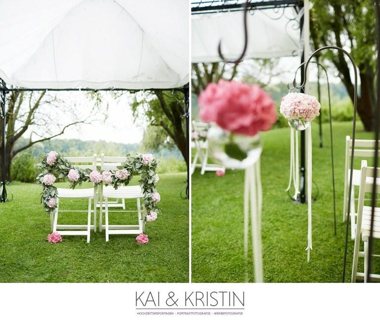 Blumen schmücken zwei weiße Stühle auf denen das Brautpaar bei ihrer freien Trauung sitzen wird