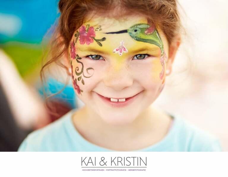 Ein kleines Mädchen mit Kinderschminke auf dem Gesicht