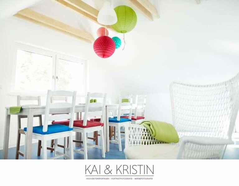 Ein schöner heller Raum mit weißen Stühlen und bunten Sitzkissen