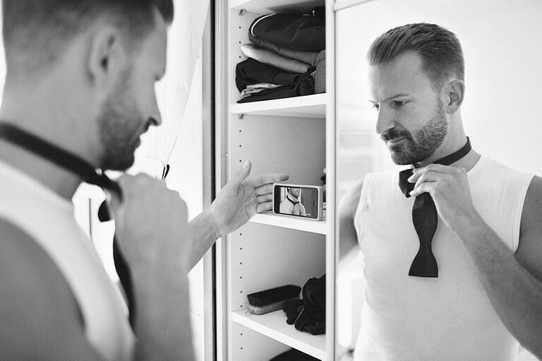Der Bräutigam schaut sich ein Video auf dem Handy an wie er sich seine Krawatte binden muss während er sich diese vorm Spiegel bindet