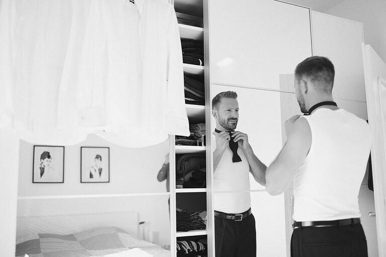 Der Bräutigam bindet sich eine Fliege vorm Spiegel