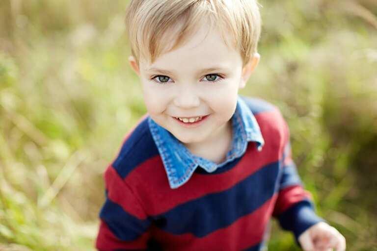 Ein kleiner blonder Junge lächelt in die Kamera