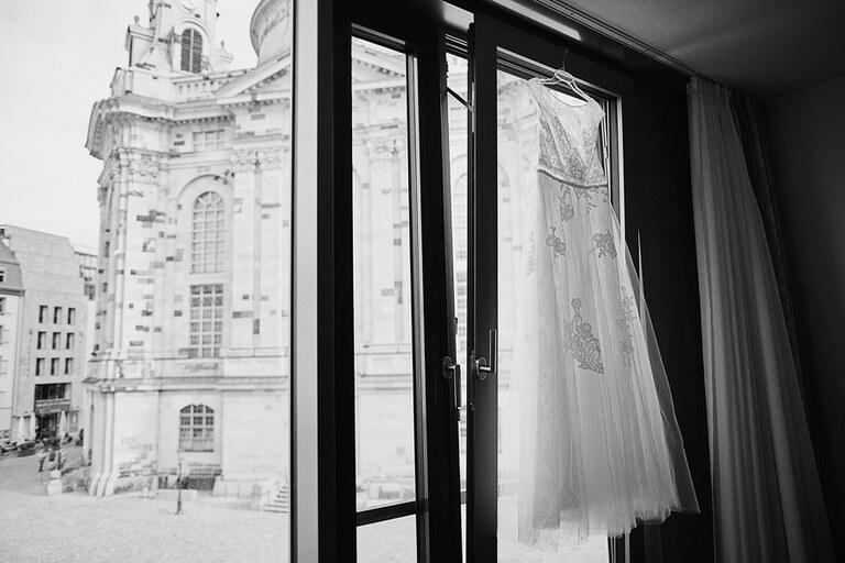 Ein Brautkleid hängt an einem Hotelfenster vor der Frauenkirche in Dresden