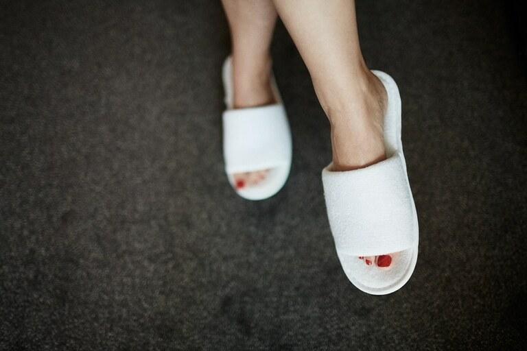 rot lackierte Füße mit Hotelschlappen