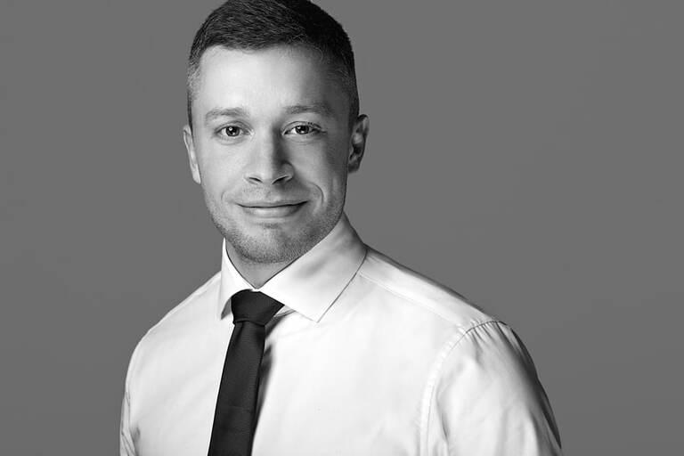 Eine Schwarz-Weiß-Aufnahme eines Mannes mit weißem Hemd und dunkler Krawatte