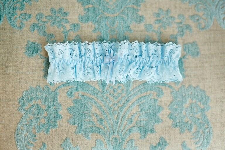 Ein blaues Strumpfband auf einem gemusterten Stoff liegend