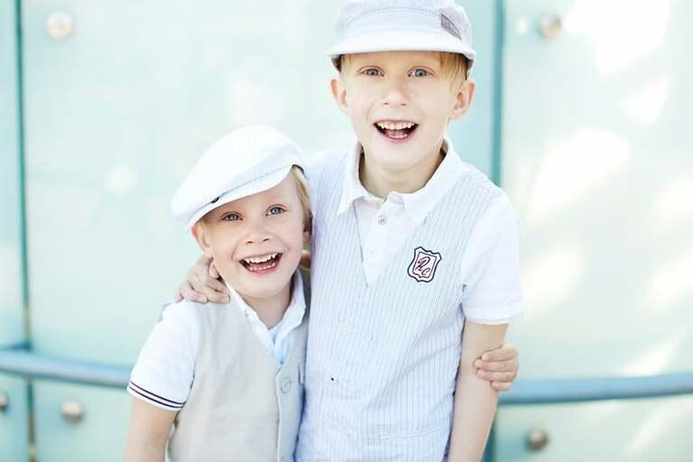 Zwei Jungs mit Mützen lachen in die Kamera während Sie sich umarmen