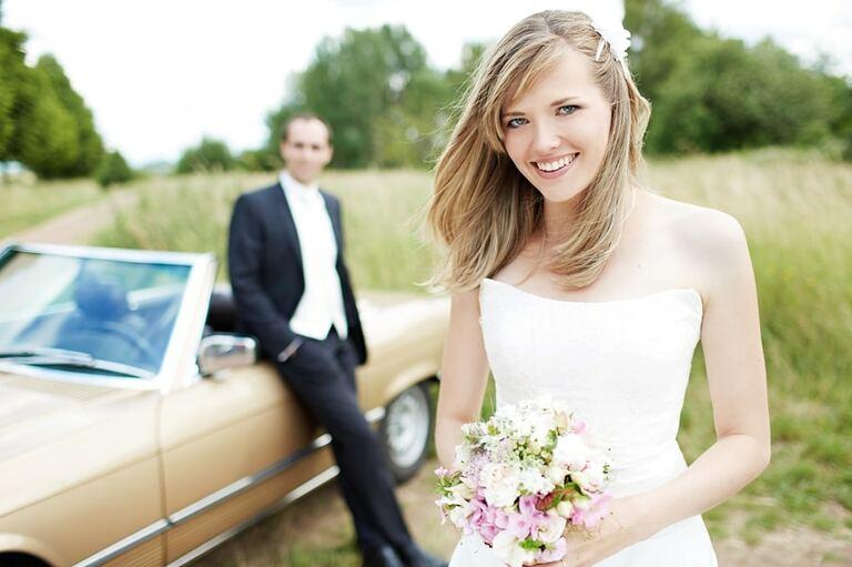 Eine Frau im Brautkleid hält einen Brautstrauß in den Händen während sich ein Mann im Hintergrund an ein Cabriolet anlehnt