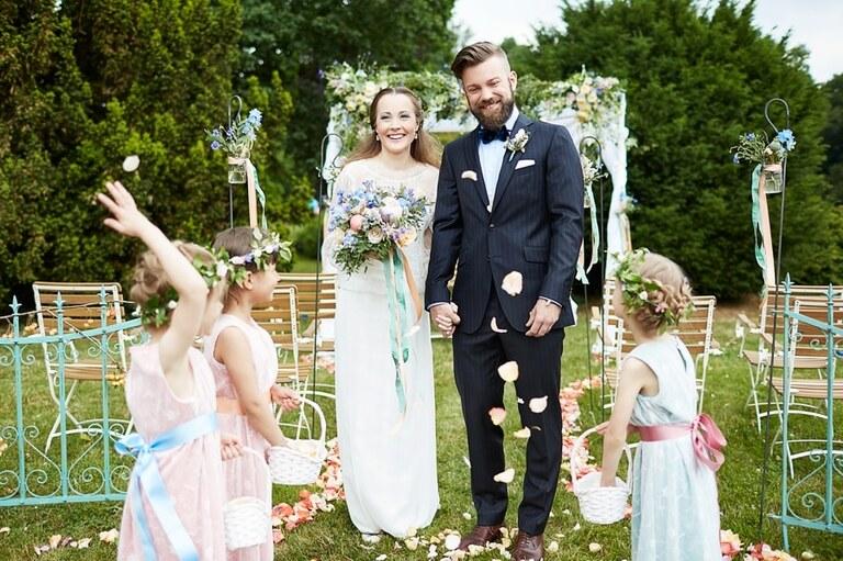 Ein Brautpaar wird von Blumenkindern mit Blüten beworfen