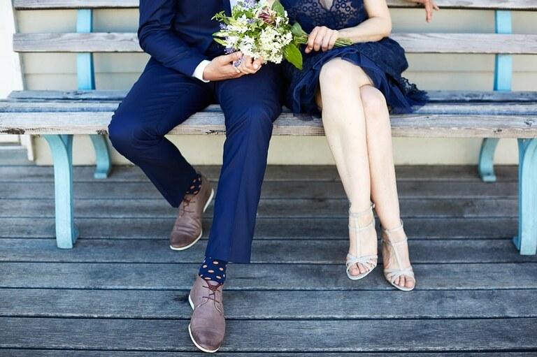 Ein Brautpaar in blauen Outfits sitzt auf einer Holzbank