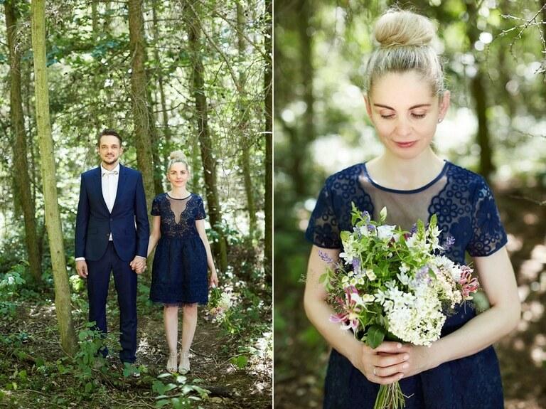 Eine Braut mit einem blauen kurzen Kleid schaut auf ihren Brautstrauß