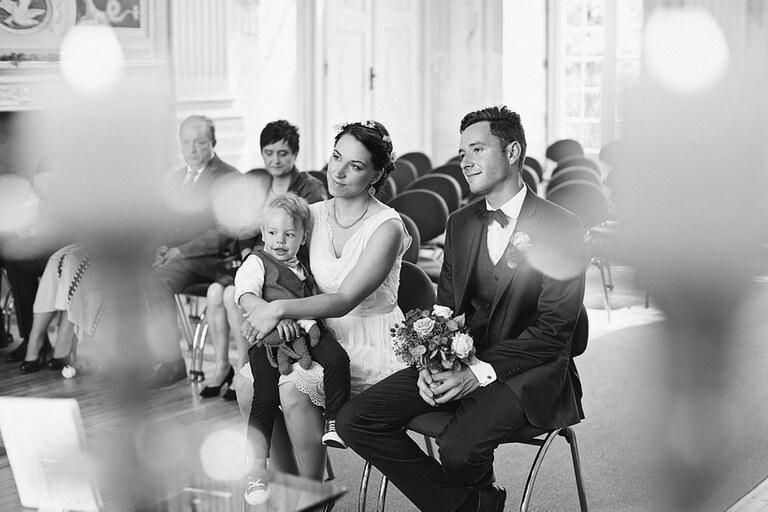 Ein Brautpaar sitzt mit seinem Sohn im Standesamt