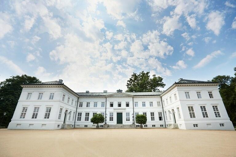 Ein weißes Herrenhaus unter blauem Himmel