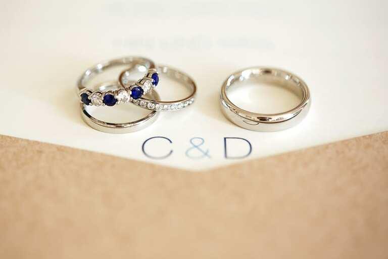 Zwei Eheringe und ein Verlobungsring auf einer karte mit den Buchstaben C und D