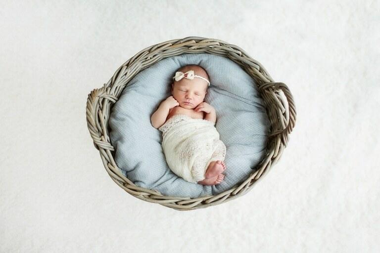 Ein Neugeborenes mit einer Schleife in einem geflochtenen Korb