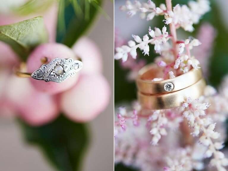 Die Eheringe an einer rosa Blüte fotografiert