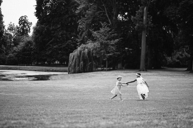 Zwei kleine Mädchen laufen spielend über eine Wiese