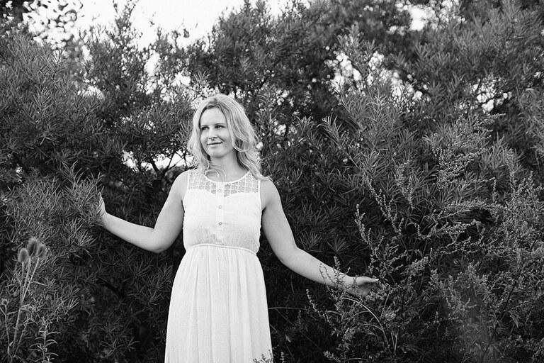 Eine blonde Frau im weißen Kleid steht im Gebüsch