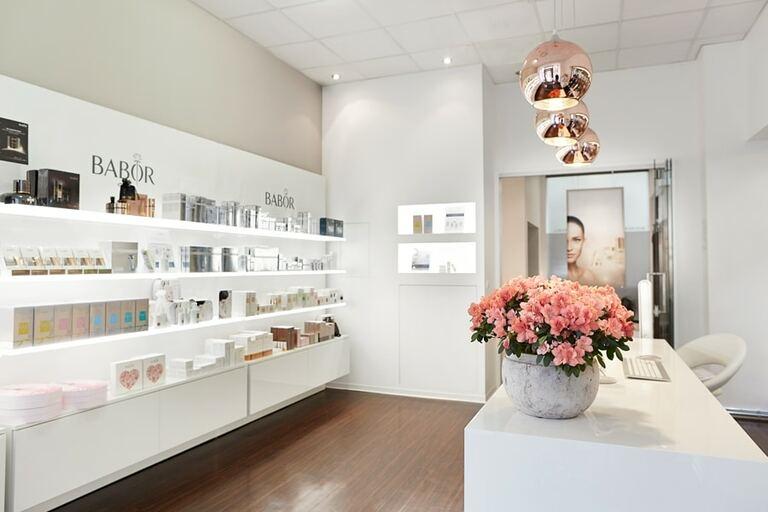 Eine Innenaufnahme von einem Kosmetikinstitut mit Regalen und Blumen auf dem Tresen