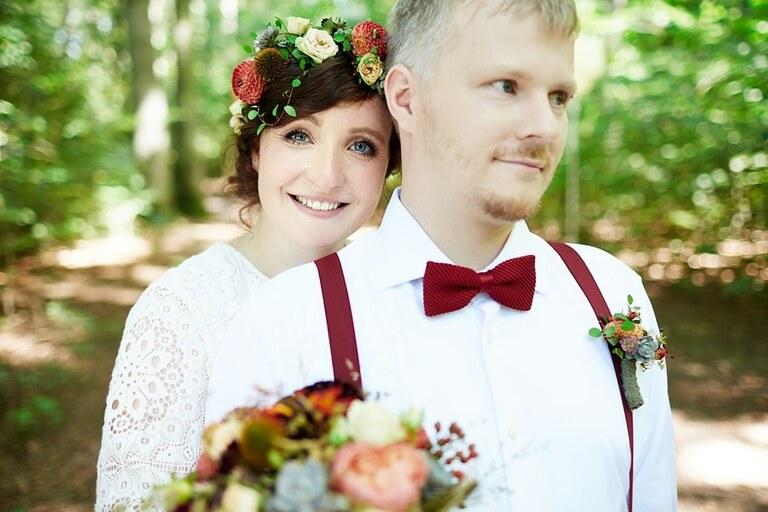 Eine Braut mit Blumenschmuck steht hinter ihrem Bräutigam der eine rote Fliege trägt