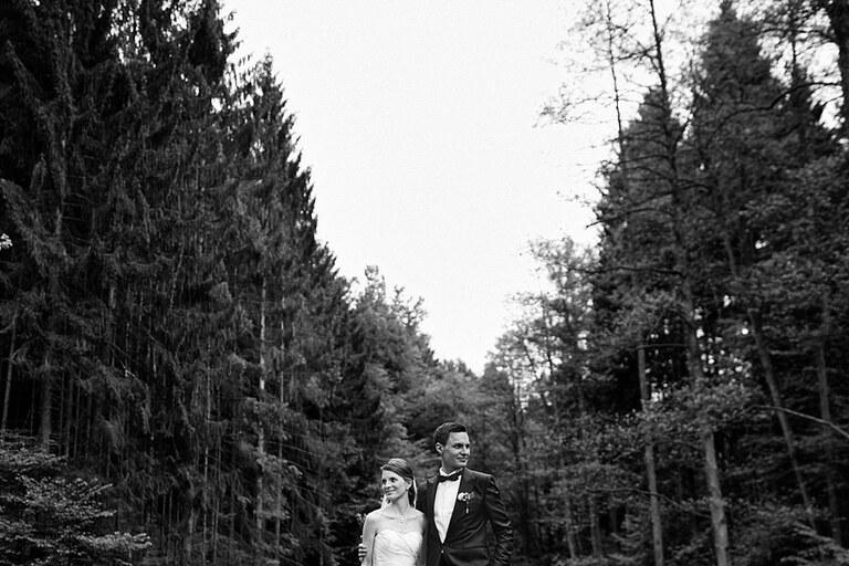 Ein Brautpaar posiert in einer Waldschneise