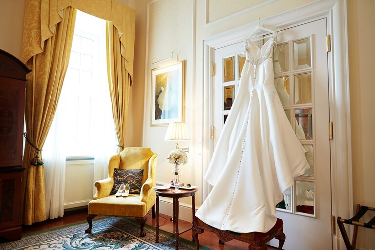Ein Brautkleid hängt im Hotelzimmer an dem Türrahmen